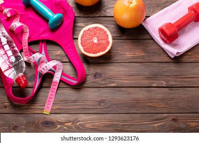 Fitness Equipment. Different tools for sport.  Sneakers and dumbbells fitness over background with copy space.  Wellness. Sports shoes on the floor, top view.- Image