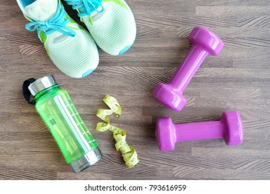 Fitness equipment, Dumbbell shoes, water bottles on wooden floor.Health and Fitness Concepts