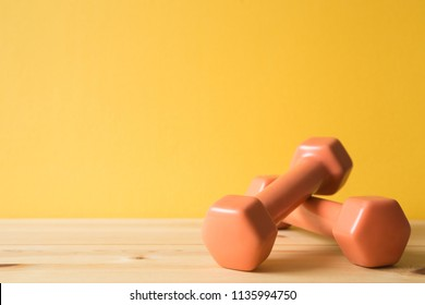 Fitness equipment dumbbells on wooden table (healthy lifestyle sport object)