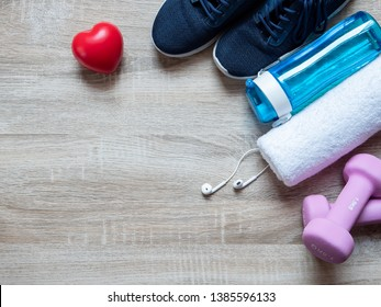 Fitness equipment with dumbbells, shoes, drinking water bottle and towel on wooden floor background. Top view from above. Health and exercise concept with copy space
