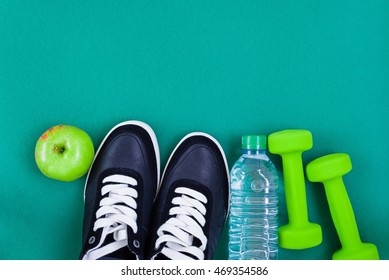 Fitness equipment. Dumbbells, sneakers, bottle of water and an apple over green background, top view