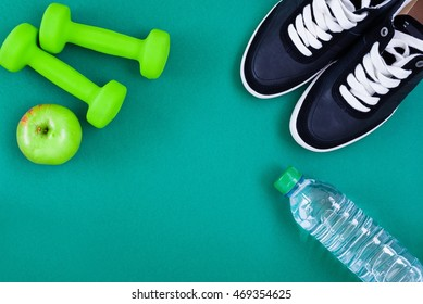 Fitness equipment. Dumbbells, sneakers, bottle of water and an apple over green background