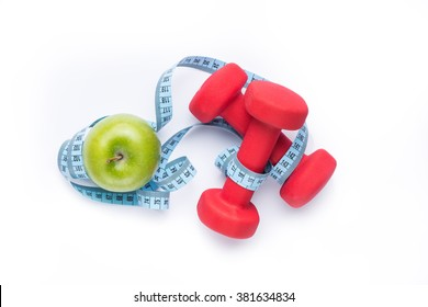 Fitness equipment. Healthy food. Apple, dumbbells and measuring tape on white background. View from above