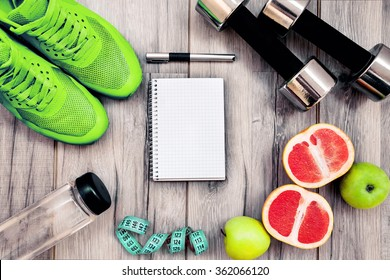 Fitness equipment. Healthy food. Sneakers, water,apple  on wooden background - Shutterstock ID 362066120
