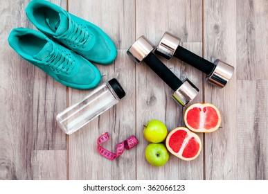 Fitness equipment. Healthy food. Sneakers, water,apple  on wooden background