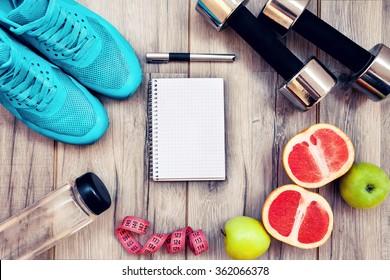 Fitnessgeräte. Gesunde Lebensmittel. Turnschuhe, Wasser, Apfel auf Holzhintergrund