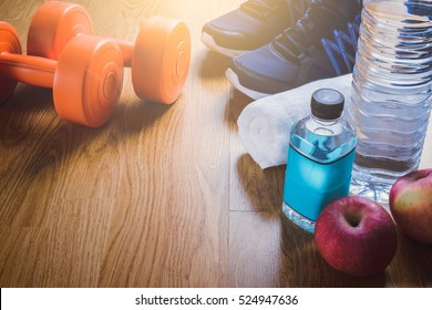 Fitness equipment. Healthy food. Sneakers, water, on wooden background