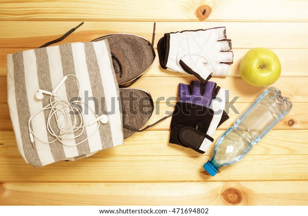 Fitness equipment. Healthy food. Sports equipment. Sportswear. Items, accessories, objects for the sport. Running shoes, sneakers,  gloves, t-shirt, water and an apple.