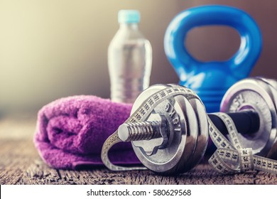 Fitness Equipment Kettlebell dumbbells towel water and measuring tape on wooden board.