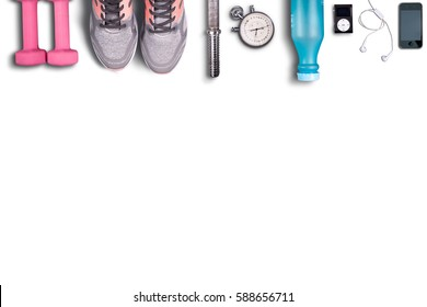 Fitness equipment on pure white background. Pink dumbbells and light shoes to running. Music for enjoyment exercises. Smartphone and fitness.