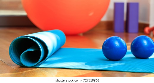 Fitness equipment. Pilates mat and exercise weights on wooden floor