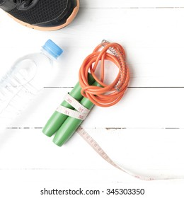 fitness equipment : running shoes,jumping rope,measuring tape and water bottle on white wood table