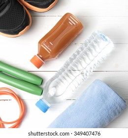 fitness equipment : running shoes,towel,jumping rope,drinking water and orange juice on white wood background