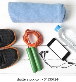 fitness equipment : running shoes,towel,jumping rope,water bottle and phone on white wood table