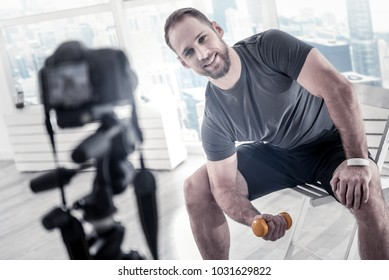 Fitness equipment. Satisfied professional male blogger sitting on chair while smiling and using dumbbell