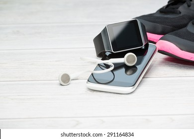 Fitness equipment, smart watch and phone on wood background.