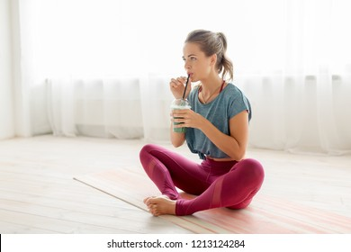 fitness equipment, sport and healthy lifestyle concept - young woman drinking from cup of smoothie at yoga studio or gym