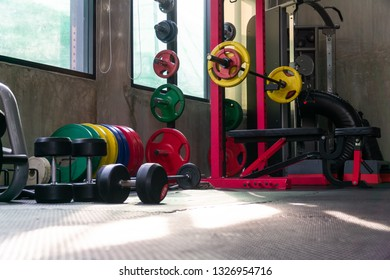Fitness equipment such as barbell, weight plates, various colors for various bench press and dumbbell positions Be prepared for an exercise class that will begin in a few minutes after this.