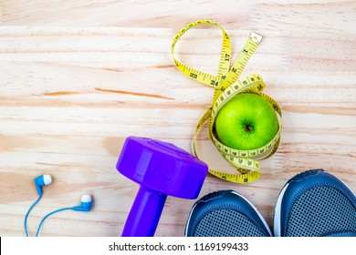 Fitness equipment with weight lifting, waist measurement, shoes and the green apples eat during exercise, put on the wood floor background .Copy space for text health care and fitness concept .