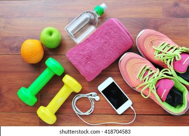 Fitness equipment,Fruit, Sneakers, water,apple on wooden floor.