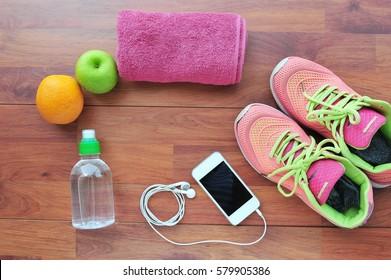 Fitness equipment,Fruit, Sneakers, water,apple on wooden floor.