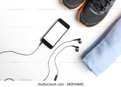 fitness equipment:running shoes,blue towel and smart phone on white wood table