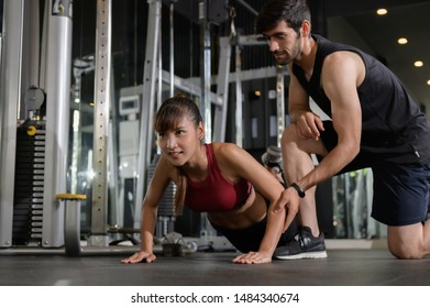 Fitness exercise or gym concept : Young beautiful Asian woman exercising with middle east fitness trainer in gym. Woman doing push ups exercise with her personal trainer at gym sport club.