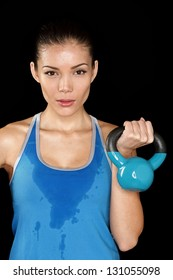 Fitness exercise woman holding kettlebell strength training biceps. Beautiful sweaty fitness instructor looking. Mixed race Asian Caucasian female sweating isolated on black background.