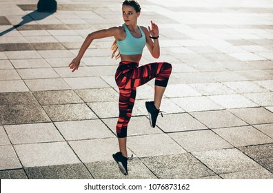 Fitness female doing cardio interval training. Caucasian woman in sportswear exercising outdoors in morning.