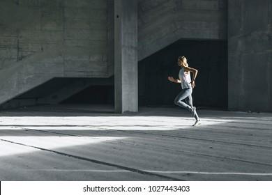 Fitness female morning run in the urban environment
