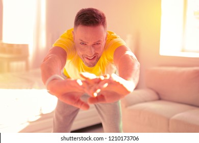 Fitness. Fit strong man doing exercises while being at home
