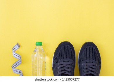 Fitness flat lay. Healthy lifestyle and sport concept. Black sneakers, tape measure and bottle of water on a yellow background.