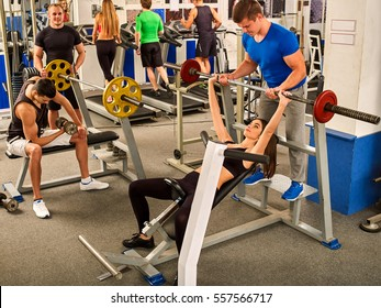 Fitness friends workout gym. Woman working on bench press. She lifting barbell. Man backs girl while taking exercises. Group work people on background