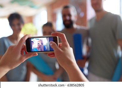 fitness, friendship and technology concept - photo of happy people at yoga studio or gym on smartphone screen