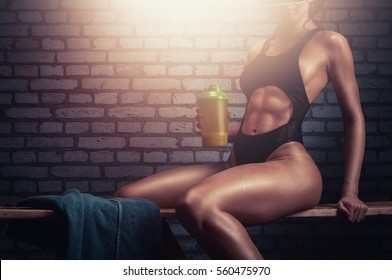 Fitness girl with athletic body taking a break after core strength training in the gym.