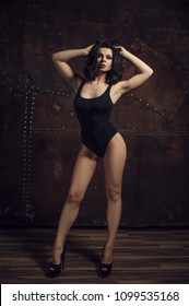 Fitness girl in black swimsuit. Trained female body.
