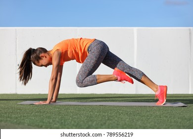 Fitness girl doing abs exercise to tone stomach muscles. Tiger curl reverse crunch planking bodyweight floor workout. Asian fit woman training outdoors on exercise mat. Gym lifestyle.