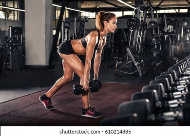 Fitness girl doing exercise with dumbbells in the gym