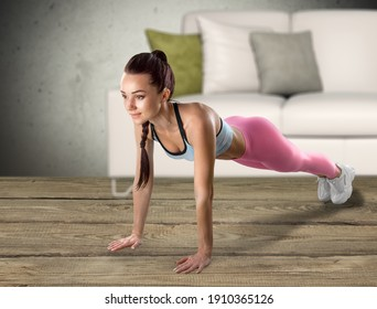 Fitness girl doing plank exercises and training muscles at home