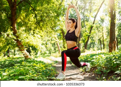 Fitness girl doing stretching warmup exercise at the park. Young woman practicing yoga. Female fitness model working out outdoor. Concept of healthy lifestyle.