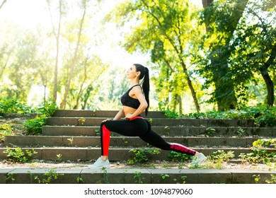 Fitness girl doing stretching warmup exercise before running at the park. Young woman practicing yoga. Female fitness model working out outdoor. Concept of healthy lifestyle.