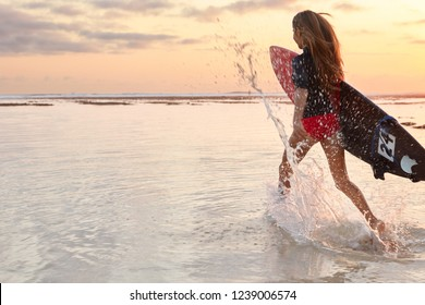 Fitness girl enjoys extreme water sport, has perfect body, runs into water, makes splashes, carries surfboard, has long hair, wears divingsuit, beautiful sky with sunset, copy space on left side