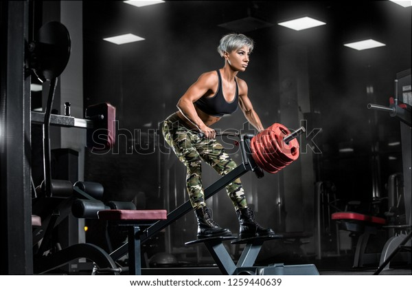 fitness girl exercising with barbell in gym