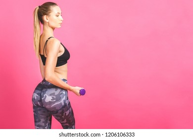 Fitness girl fit woman with dumbbells, doing exercise with dumb bells training with weights isolated on pink background.