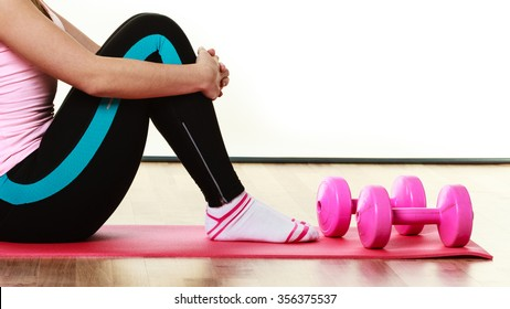 Fitness girl fit woman sitting on exercise mat with dumbbells, doing exercise with dumb bells training isolated