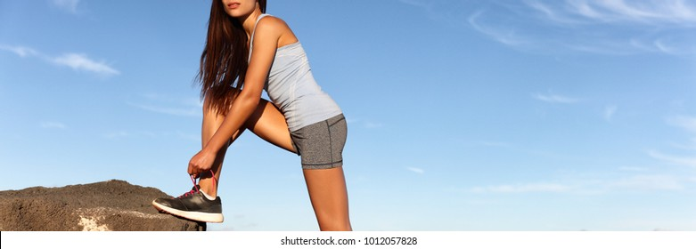 Fitness girl getting ready to run tying running shoe laces outdoor in sky blue background banner panorama. Woman training outside doing cardio exercise.