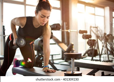 Fitness girl lifting dumbbell in the morning.
