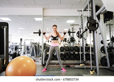 Fitness girl making squat with a barbell in the gym
