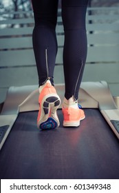 Fitness girl with muscular legs running on treadmill in the gym