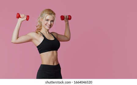 Fitness girl with perfect slim and fit body training muscles with dumbbells on pink background. Sporty woman in sportswear